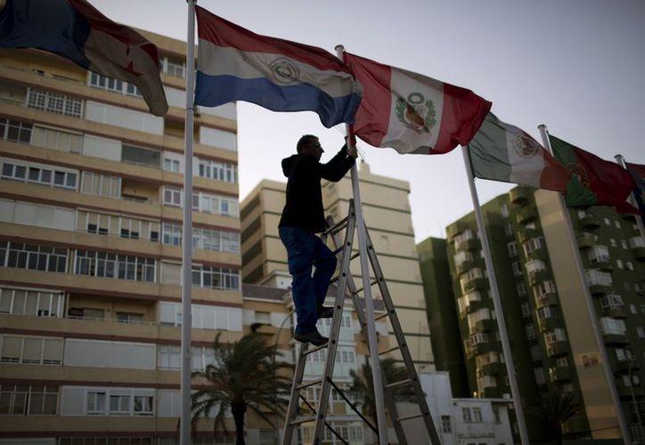 Un trabajador ajusta las banderas de los países de América Latina, de cara a la Cumbre Iberoamericana en la entrada de Cádiz, España. (Agencias)