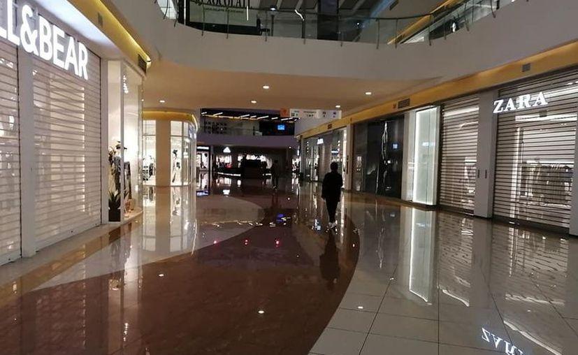 En plazas comerciales, algunas tiendas continúan operando. (Novedades Yucatán)