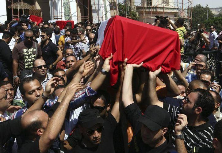 Policías portan los ataúdes de los policías egipcios que fallecieron en los enfrentamientos entre manifestantes y policías en El Cairo hoy. (EFE)