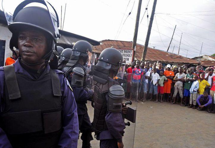 Fuerzas de seguridad liberianas controlan una multitud en el barrio pobre de West Point, para impedir que se extienda el brote de ébola. (Agencias)