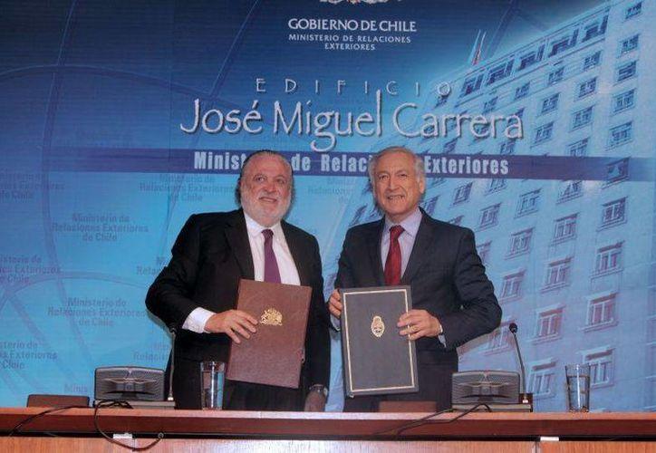 El embajador de Argentina en Chile, Ginés González (izq), y el canciller chileno Heraldo Muñoz tras firmar el acuerdo para la construcción del túnel. (publimetro.cl)