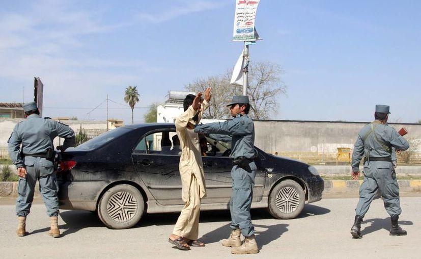 Policías afganos registran a un hombre en Jalalabad, Afganistán tras las violentas protestas en contra de la profanación de un corán en marzo de 2013. (Archivo/EFE)