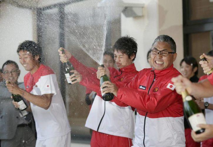 Los japoneses Minoru Ueda (d) y Kei Nishikori (C) celebran la primera victoria de Japón en las rondas decisivas de la Copa Davis. (EFE)
