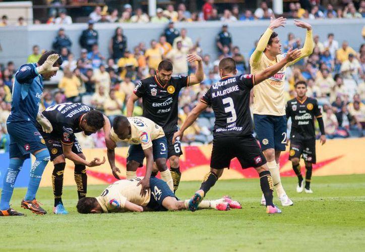 Tras chocar su cabeza con la cadera del arquero de Leones Negros, Oribe Peralta quedó tendido sobre el pasto pero después siguió jugando el partido. (Notimex)