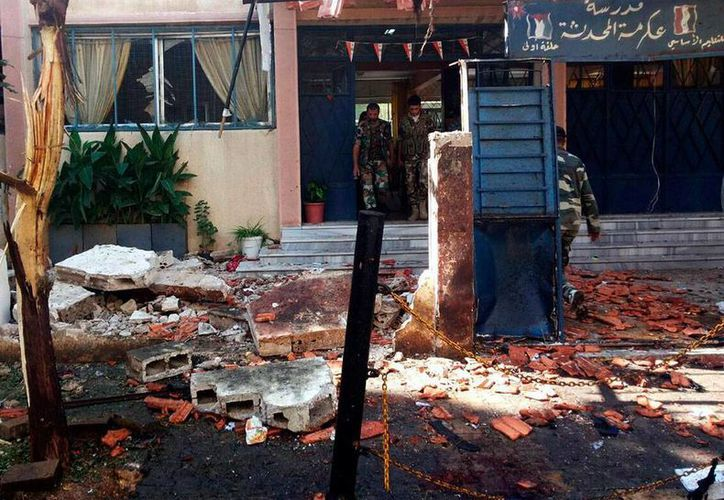 Fuerzas de seguridad inspeccionan los daños ocasionados por una explosión en una escuela primaria de Homs, Siria. Hasta ahora, las autoridades no han informado cuántos niños murieron. (Efe/Sana)