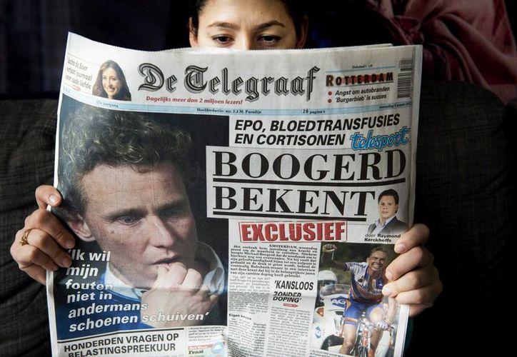 Una mujer lee un ejemplar de De Telegraaf publicado hoy, que muestra en portada una fotografía del exciclista Michael Boogerd que confesó haberse dopado durante su carrera. (EFE)