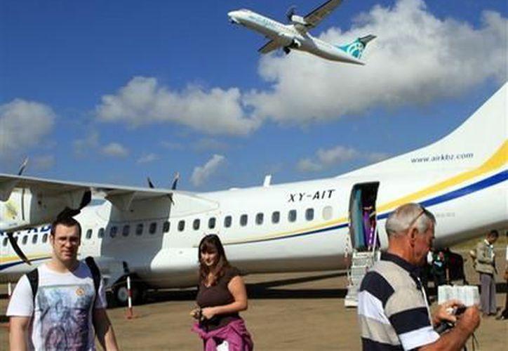 En esta fotografía del 9 de noviembre de 2011, un avión de Air Bagan despega mientras varios turistas llegan al aeropuerto de Heho. (Agencias)