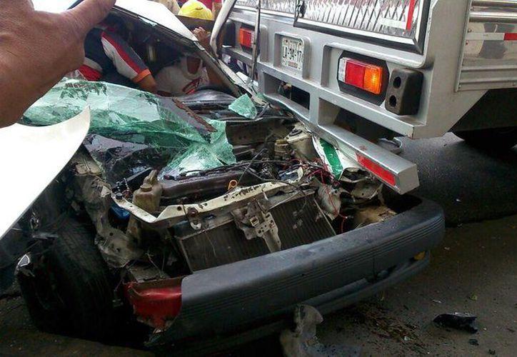 Para sacar al taxista de la unidad se requirió de la ayuda de los bomberos en el lugar del accidente. (Redacción/SIPSE)
