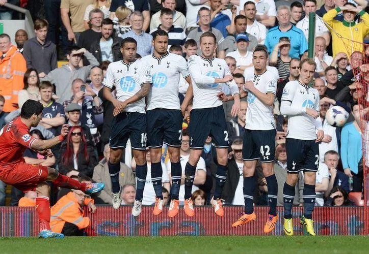 El delantero del Liverpool Luis Suarez (i) cobra un penal en el partido ante el Tottenham en Anfield Road. (EFE)