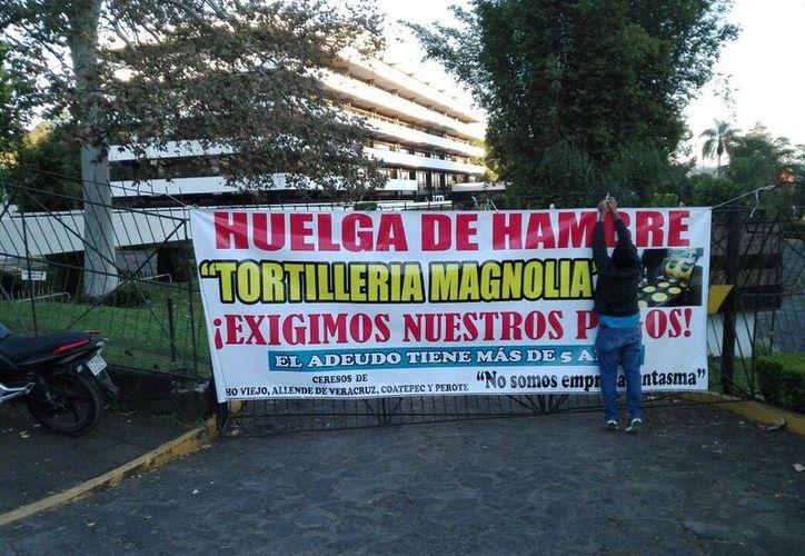 Los trabajadores de la tortillería 'Magnolia' colocaron una lona en la entrada de las oficinas de la Secretaría de Finanzas y Planeación para exigir el dinero que se les debe. (twitter.com/RamsesChama)