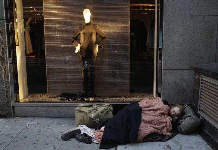 Un hombre duerme afuera de una tienda de lujo en Nueva York. (Archivo/AP)