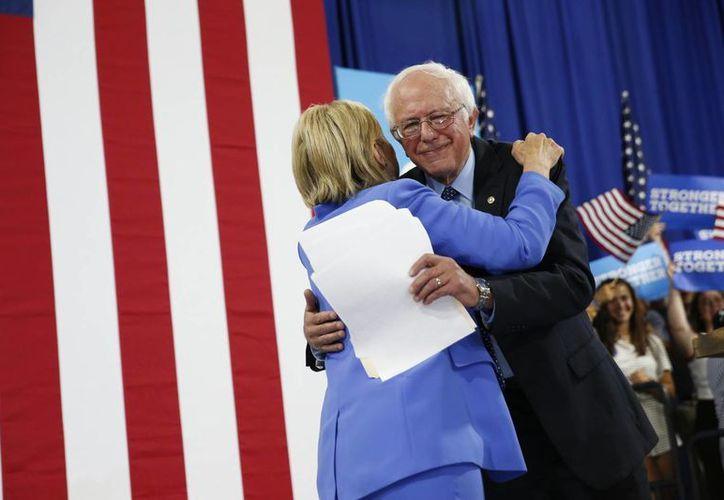 El senador Bernie Sanders abraza a la candidata demócrata a la presidencia de EU, Hillary Clinton, durante un acto de campaña. (Agencias)