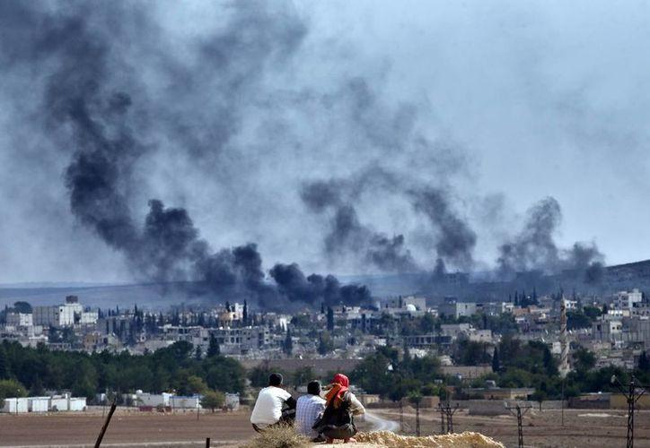 Refugiados kurdos sirios de Kobani presencian los combates en Kobani, al otro lado de la frontera, desde una colina a las afueras de Suruc, en Turquía, cerca de la frontera con Siria. (Agencias)