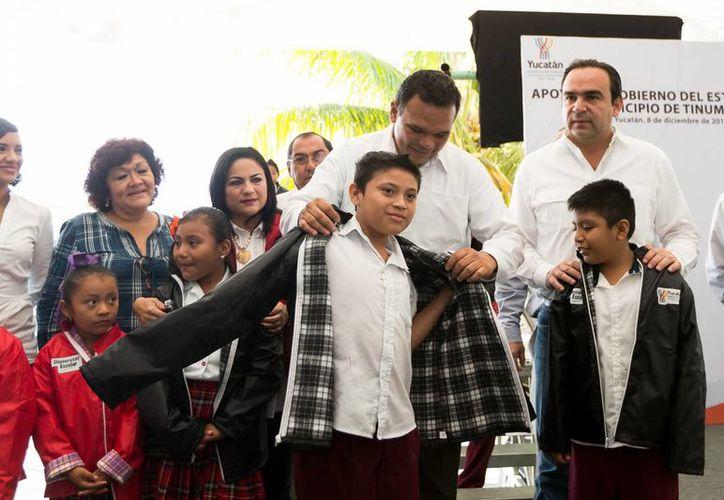 Imagen del inicio de la fase invernal del plan Bienestar Escolar en Tinum. El Gobernador le coloca una chamarra a uno de los niños beneficiados. (Milenio Novedades)