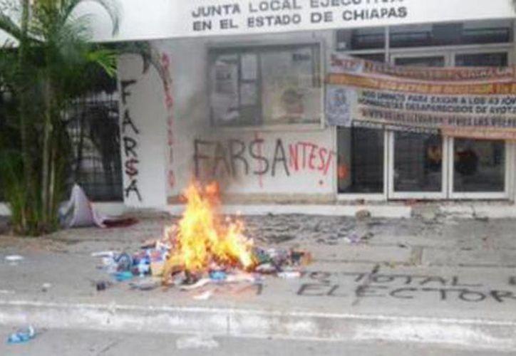 Los miembros de la CNTE en Chiapas tomaron las instalaciones del INE como parte de su 'boicot electoral. Imagen de la quema de boletas en Tuxtla Gutierrez. (@AristeguiOnline).