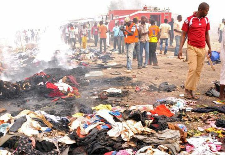 Rescatistas y curiosos se reúnen en el lugar de la explosión de dos coches bomba ayer, en un concurrido mercado de la ciudad de Jos, Nigeria. (EFE)