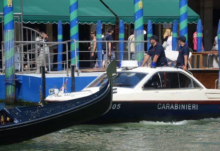 Oficiales de la policía paramilitar italiana patrullan a bordo de un bote por el Gran Canal de Venecia, Italia. (Agencias)