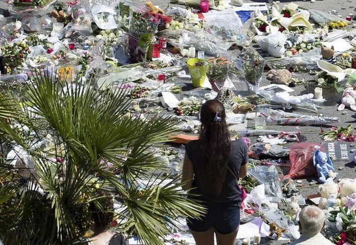 Se ha identificado formalmente a 35 de los 84 muertos del atentado de Niza. En la imagen, una mujer junto al monumento improvisado de flores y velas en el 'Paseo de los Ingleses', lugar del atentado.- (EFE)