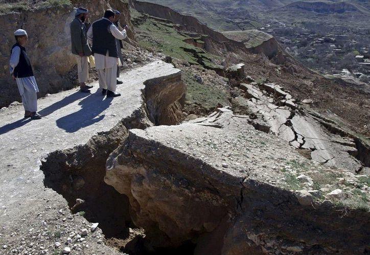 Varias personas observan los destrozos causados en una carretera tras un desgajamiento de tierras en el distrito afgano de Marmol. (EFE/Foto de archivo)
