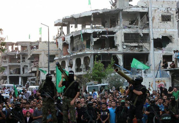 Palestinos observan a los milicianos de Ezz Al-Din Al Qassam, rama militar de Hamas, posando con sus armas en medio de viviendas destruidas en el barrio de Al-Shejaeiya, al este de Gaza. (Archivo/EFE)