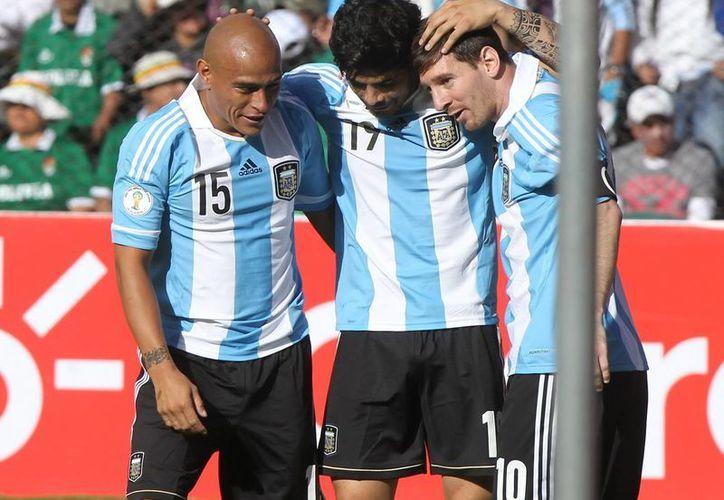El argentino Ever Banegas (c) celebra su gol ante Bolivia con sus compañeros Clemente Rodríguez (i) y Lionel Messi (d). (EFE)