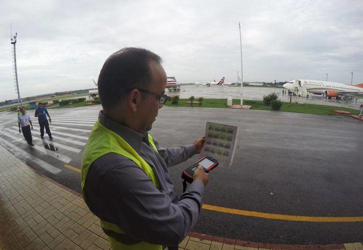 Galo Beltrán, gerente de American Airlines en Cuba, ensaya un scanner de equipaje en el aeropuerto José Martí de La Habana. (Agencias)