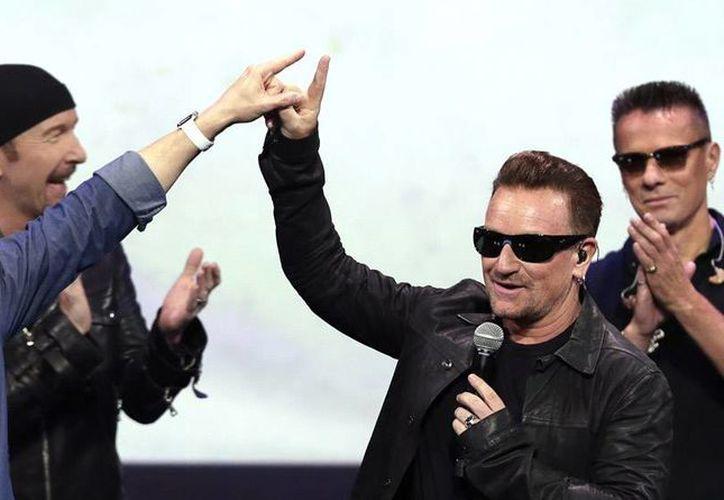 Tim Cook de Apple acompañado de los integrantes de la banda de U2 liderada por Bono, el pasado martes. (Agencias)