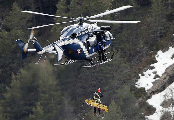 Imagen del rescate de un cadáver en un helicóptero en la escena de un accidente aéreo en Francia. Decenas de familiares de las víctimas del choque de Germanwings en los Alpes franceses esperan el regreso de los restos de sus seres queridos. (Foto AP/Laurent Cipriani, Archivo)