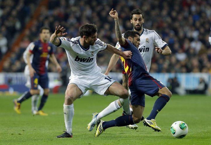 Dani Alves (con el balón) dice que se debería seguir el ejemplo del futbol en Inglaterra. (AP)