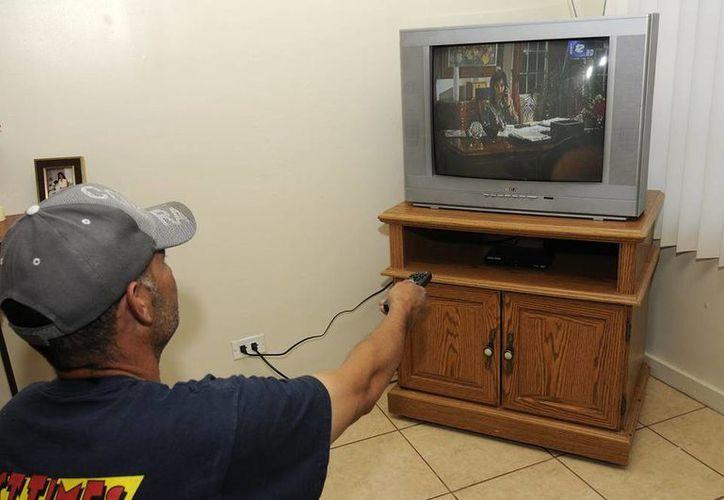 El apagón analógico se realizará en todo el país a más tardar el 31 de diciembre de 2015. Imagen de un hombre que mira una televisión analógica. (starmedia.com)