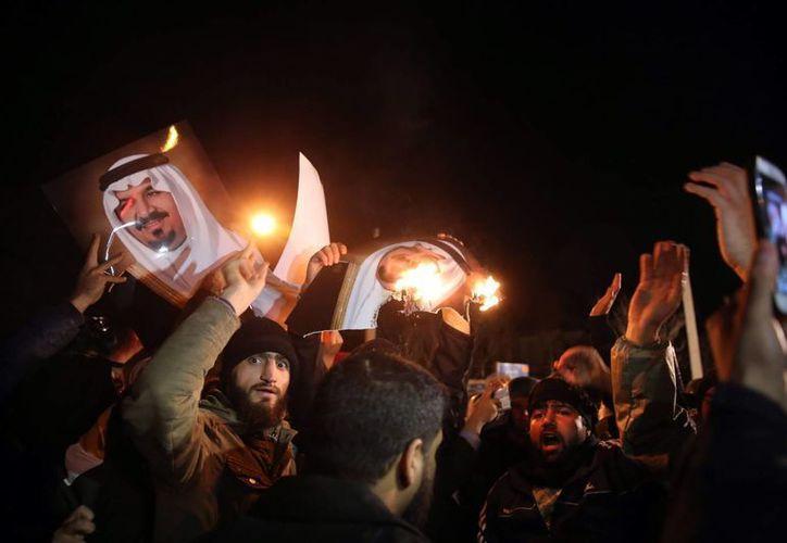 Un grupo quema fotos de miembros de la familia real saudí frente de la embajada de Arabia en Teherán, Irán. (EFE)