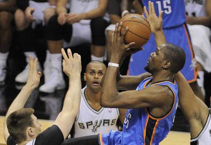 Kevin Durant (d), del Thunder, lanza a la canasta mientras lo acosa el australIano Aron Baynes, de Spurs, en la segunda mitad del primer juego de la serie final de la Conferencia Oeste. (Foto: AP)