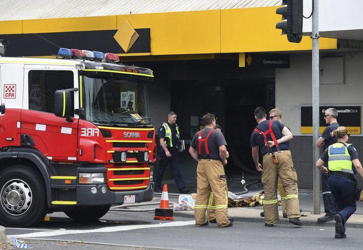 Miembros de los servicios de rescate se reúnen en la filial del Banco Commonwealth en Melbourne, Australia, donde un hombre se quemó y provocó un incendio, el 18 de noviembre de 2016. (EFE)