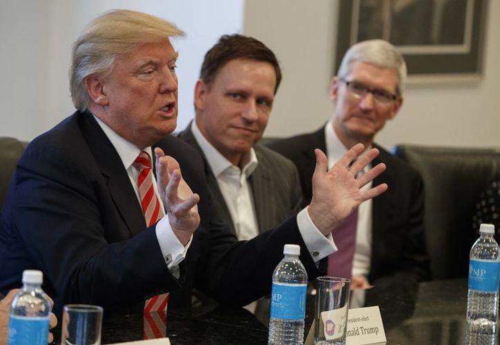 El director ejecutivo de Apple Tim Cook, derecha, y el fundador de PayPal Peter Thiel, centro, escuchan al presidente electo Donald Trump durante una reunión con líderes de tecnología en Trump Tower, en Nueva York, este miércoles 14 de diciembre de 2016. (AP Foto/Evan Vucci)