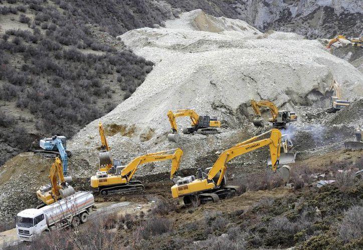 En esta fotografìa divulgada por la Agencia de Noticias Xinhua de China, varias palas mecánicas retiran lodo, rocas y escombros en el lugar del alud. (Agencias)