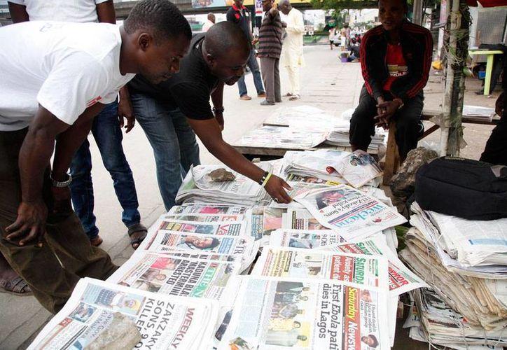 Ciudadano de Lagos, la ciudad más poblada de Nigeria, revisan las últimas noticias en los impresos que le dieron vuelo a la nota sobre la muerte, por ébola, de un ciudadano de Libera. (AP)