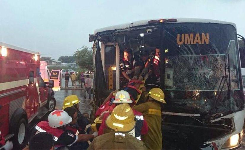 Bomberos tuvieron que intervenir para rescatar a los pasajeros del autobús que se impactó contra un tráiler, en la Avenida Internacional de Mérida. (SIPSE)