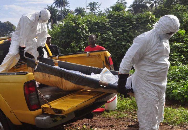 Trabajadores de salud llevan el cuerpo de una víctima de ébola a una fosa, en las afueras de Monrovia, Liberia, el 27 de octubre de 2014. (Foto: AP)