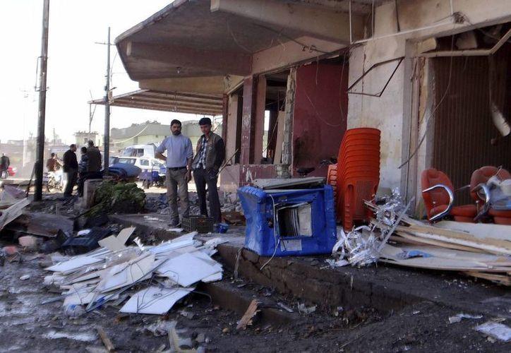 Iraquíes inspeccionan los daños causados por la explosión de un coche bomba en Tuz Khormato, en la provincia de Saladin, Irak. (EFE)