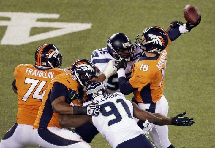 El quarterback Peyton Manning de los Broncos de Denver es impactado por Cliff Avril (56) de los Seahawks de Seattle durante el primer tiempo del Super Bowl. (Agencias)