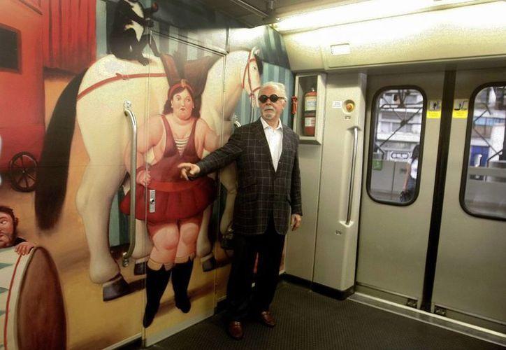 El maestro colombiano Fernando Botero fue registrado este viernes en un vagón del metro en Medellín Colombia, junto a una réplica de una de sus pinturas de la exposición 'El Circo'. (EFE)