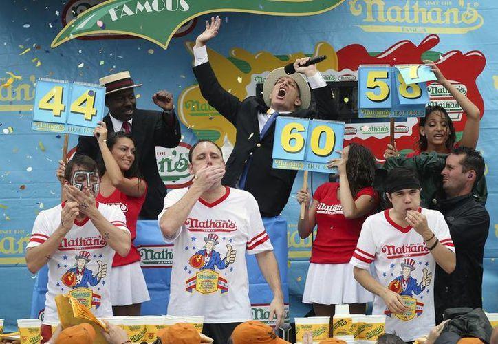 Joey Chestnut (en medio) resultó ganador de la 99na edición de este concurso anual en la playa neoyorquina de Coney Island, Nueva York. En la foto acompañado de sus contrincantes Tim Janus (izq) y Matt Stonie (der). (Agencias)