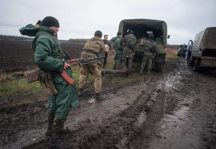 Un soldado ucraniano monta guardia (i) mientras un convoy militar se detiene para cargar suministros, cerca de Donetsk, en abril. (EFE)