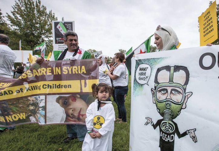 Los manifestantes opuestos al gobierno del presidente sirio Bashar Assad se reúnen en el césped del Capitolio en Washington. (Agencias)