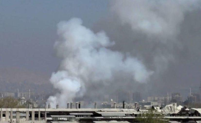 Humo se levanta sobre edificios atacados en Damasco. (Agencias)
