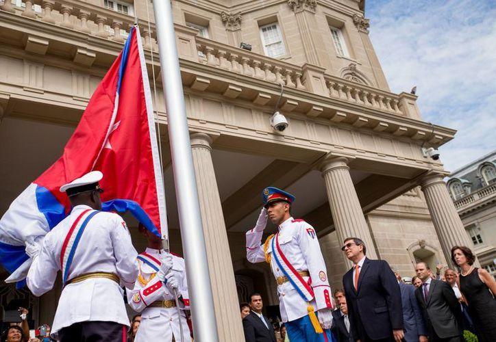 El reloj marcaba exactamente las 10:36 horas del lunes 20 de julio de 2015 cuando oficiales cubanos izaron la bandera de Cuba en el edificio que funcionó como sección de intereses desde la década de 1970. (Foto: AP)