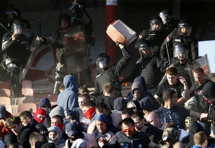 Policías antidisturbios serbios se enfrentan con seguidores del club Estrella Roja de Belgrado durante el partido contra el Partizan, este sábado. (Foto AP/Darko Vojinovic)