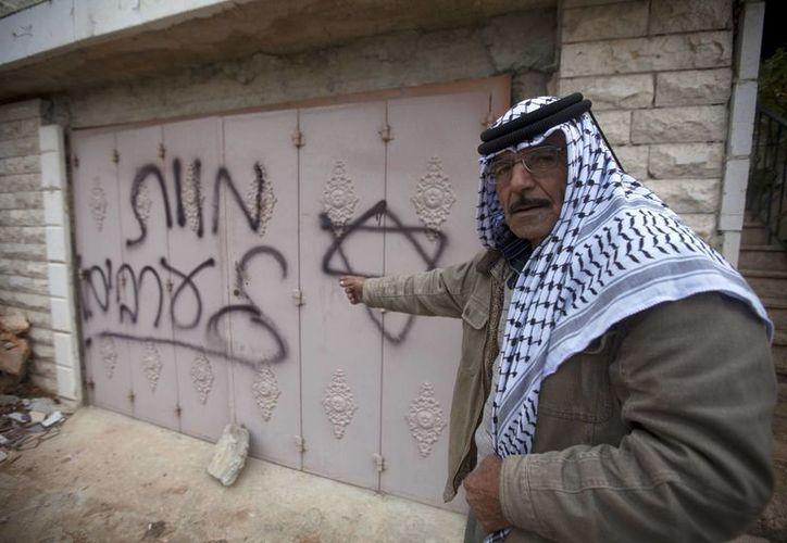"""Un hombre señala a los palestinos por escribir un graffiti con consignas hebreas """"Muerte a los árabes""""; tras un incendio provocado en  la ciudad cisjordana de Ramala. (Agencias)"""
