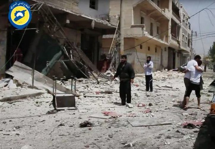 Un hombre ayuda a un herido mientras otros están de pie entre los escombros tras bombardeos sobre Alepo, Siria. (Agencias)