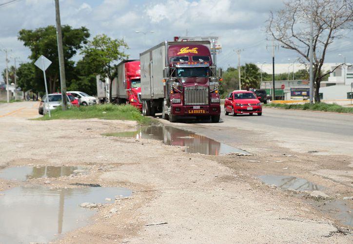 Grandes baches cubren buena parte de la carretera que comunica a la zona industrial de Umán. (Jorge Acosta/Milenio Novedades)
